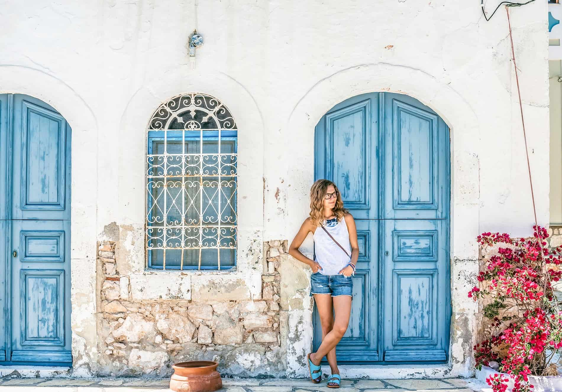 Young woman at typical greek traditional town with colorful buildings on Greek Island, Greece, Europe